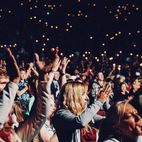 Crowds at a concert event clapping their hands